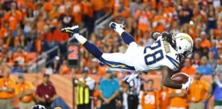 Los Angeles Chargers running back Melvin Gordon (31) leaps over Denver Broncos safety Justin Simmons (31) to score in the second quarter at Sports Authority Field.