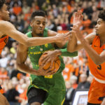 Oregon Ducks forward Troy Brown (0) drives between Oregon State Beavers guard Stephen Thompson Jr. (1) and guard Ethan Thompson (5) during the first half during a game at Gill Coliseum