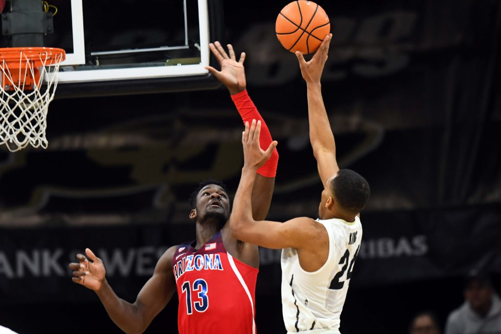 Colorado Buffaloes guard George King (24) attempts a basket over Arizona Wildcats forward Deandre Ayton (13) in the second half at the Coors Events Center.