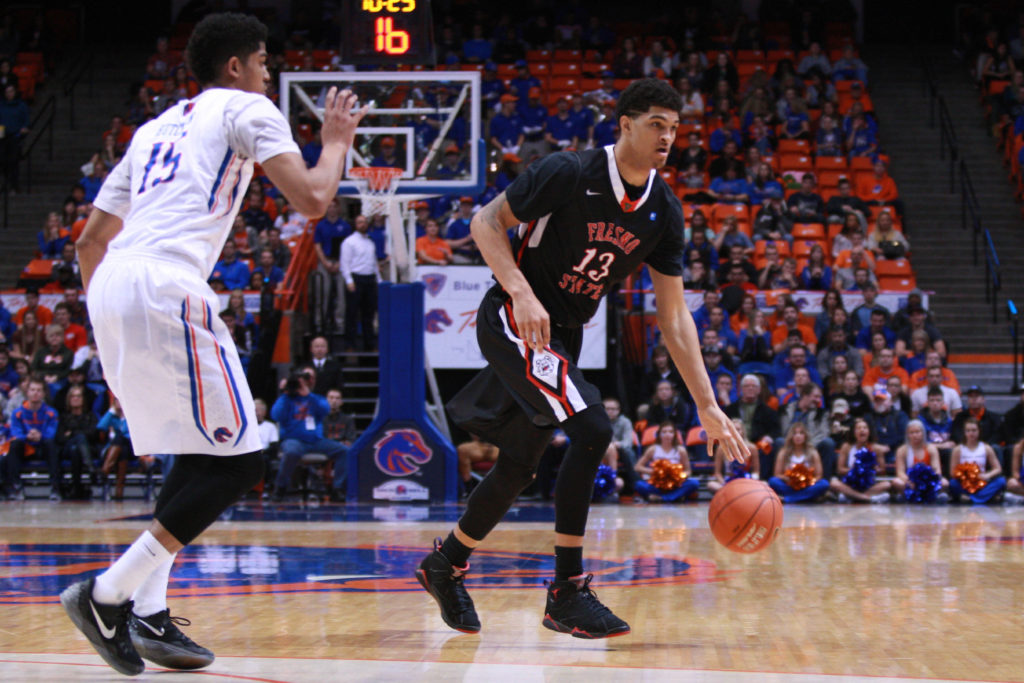 Fresno State Bulldogs forward Cullen Russo (13) dribbles on the perimeter against Boise State Broncos forward Chandler Hutchinson (15) during first half at Taco Bell Arena.