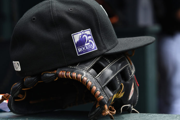 eneral view of a cap and glove for Colorado Rockies marking the twenty fifth anniversary emblem of the team during the game Los Angeles Dodgers at Coors Field. Mandatory Credit: Ron Chenoy-USA TODAY Sports