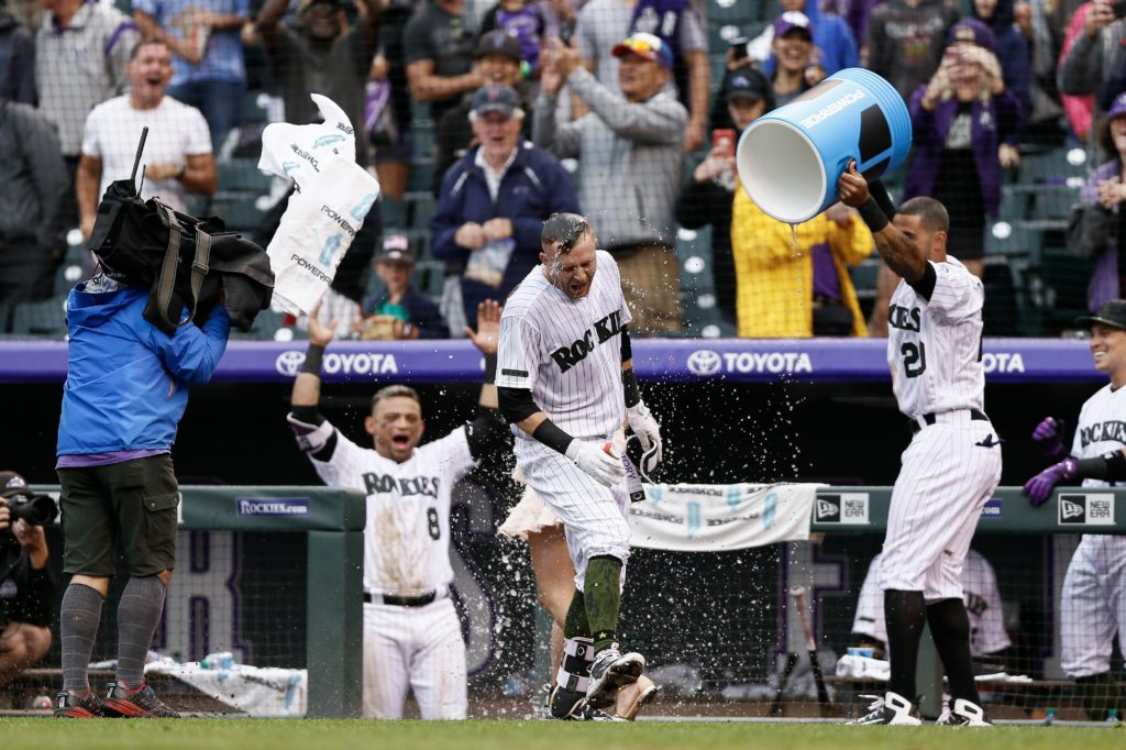 Jul 15, 2018; Denver, CO, USA; Colorado Rockies first baseman Ian Desmond (20) douses shortstop Trevor Story (27) as he is interviewed after a walk off home run in the ninth inning against the Seattle Mariners at Coors Field. Mandatory Credit: Isaiah J. Downing-USA TODAY Sports