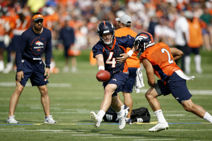 Denver Broncos quarterback Case Keenum (4) hands the ball off to running back Phillip Lindsay (2) during a drill on the first day of training camp at Paul D. Bowlen Memorial Broncos Centre.