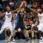 Orlando Magic center Nikola Vucevic (9) controls the ball against Denver Nuggets forward Darrell Arthur (00) and forward Kenneth Faried (35) in the second quarter at Pepsi Center.