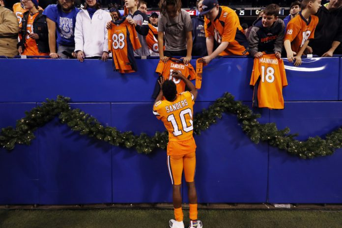 Denver Broncos wide receiver Emmanuel Sanders (10) signs autographs after the game against the Indianapolis Colts at Lucas Oil Stadium.