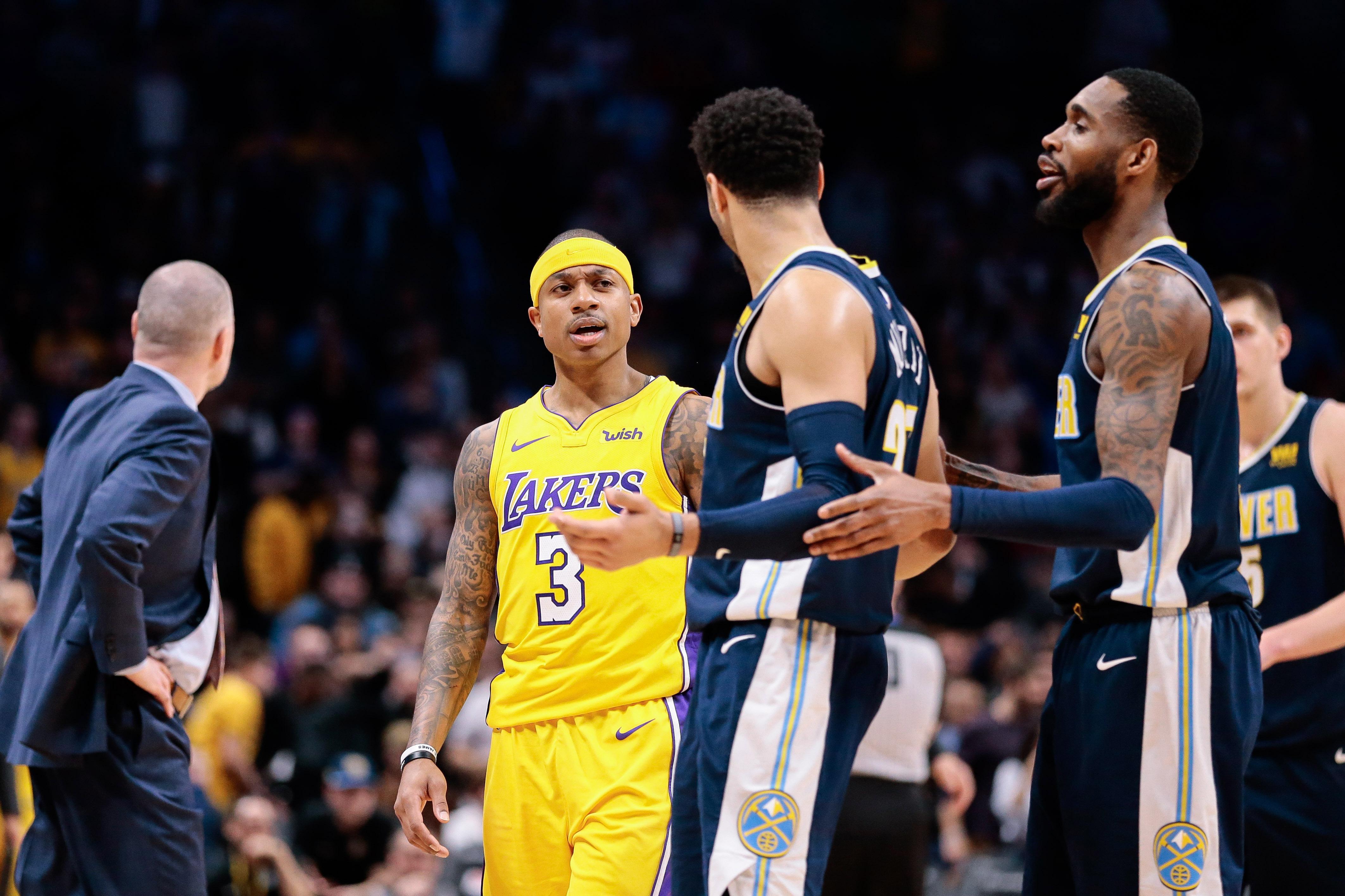 Denver Nuggets forward Will Barton (5) separates guard Jamal Murray (27) from Los Angeles Lakers guard Isaiah Thomas (3) after the game at the Pepsi Center.