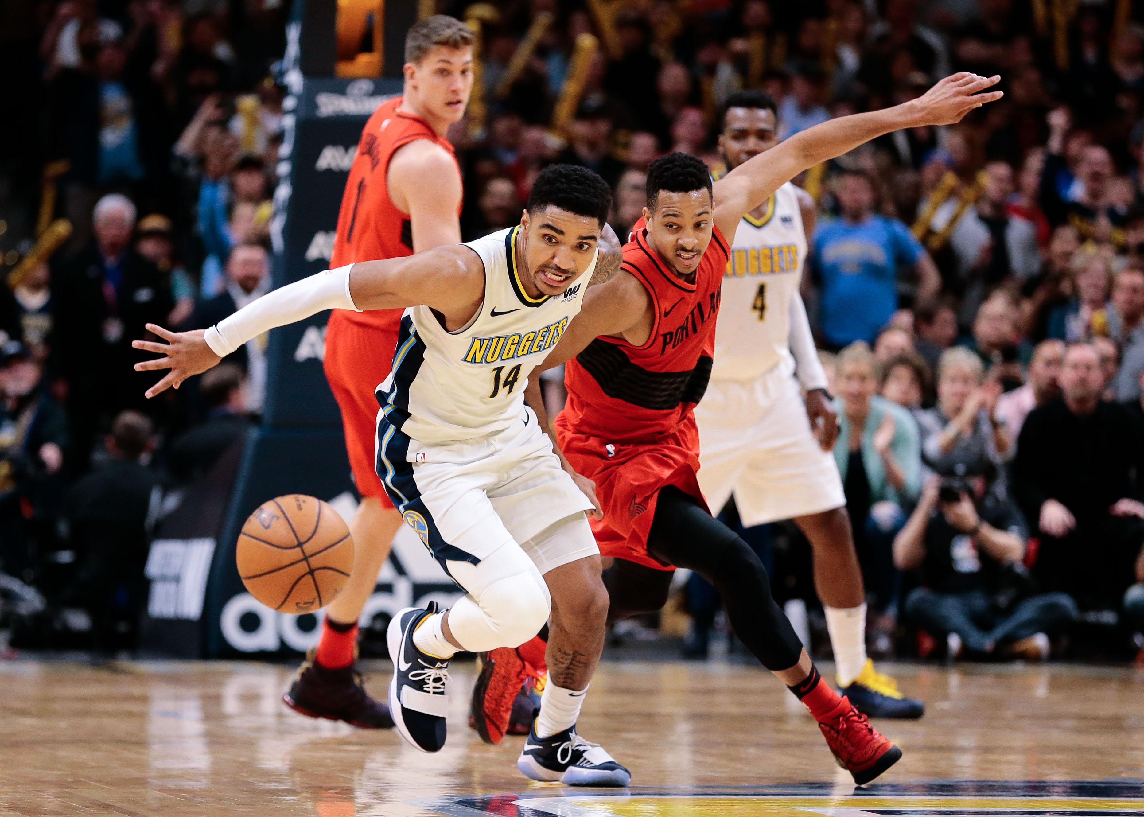 Denver Nuggets guard Gary Harris (14) and Portland Trail Blazers guard CJ McCollum (3) battle for a loose ball in the fourth quarter at the Pepsi Center.