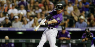 Colorado Rockies third baseman Ryan McMahon (24) hits a two run home run in the seventh inning against the Los Angeles Dodgers at Coors Field.