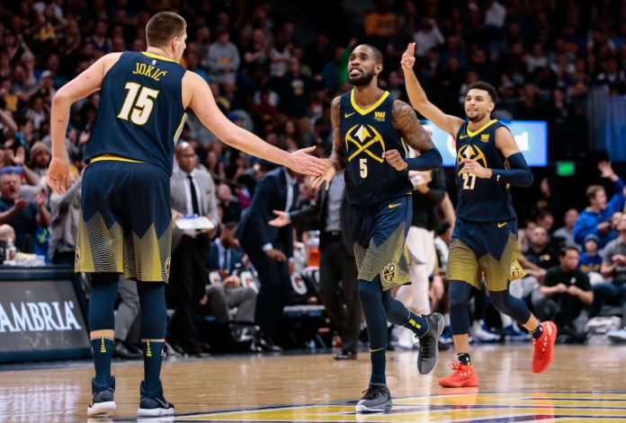 Denver Nuggets guard Will Barton (5) and center Nikola Jokic (15) and guard Jamal Murray (27) celebrate after a play in the fourth quarter against the Golden State Warriors at the Pepsi Center.