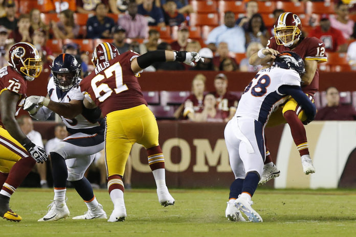 Washington Redskins quarterback Colt McCoy (12) is hit by Denver Broncos linebacker Von Miller (58) while passing the ball in the second quarter at FedEx Field.