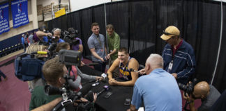 Denver Nuggets center Nikola Jokic (15) answers questions during media day at the Pepsi Center.
