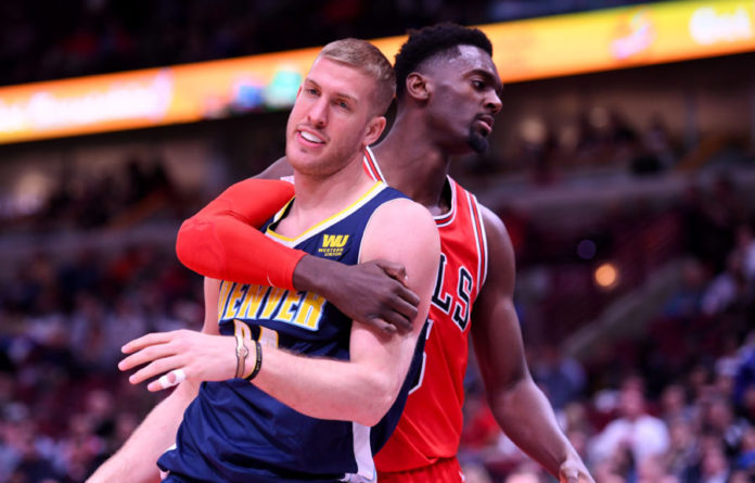 Chicago Bulls forward Bobby Portis (5) fouls Denver Nuggets center Mason Plumlee (24) during the second half at the United Center.