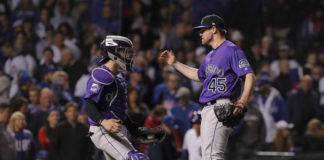 Colorado Rockies players Tony Wolters (left) and Scott Oberg (45) celebrate after defeating the Chicago Cubs in the 2018 National League wild card playoff baseball game at Wrigley Field.