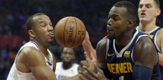 LA Clippers guard Avery Bradley (11) and Denver Nuggets forward Paul Millsap (4) battle for a loose ball during the third quarter at Staples Center.
