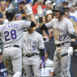 Colorado Rockies third baseman Nolan Arenado (28) is greeted by shortstop Trevor Story (27) after hitting a solo home run in the eleventh inning against the Milwaukee Brewers at Miller Park.
