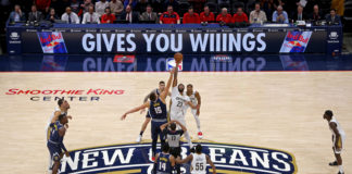 Denver Nuggets center Nikola Jokic (15) jumps with New Orleans Pelicans forward Anthony Davis (23) to start the game at the Smoothie King Center.