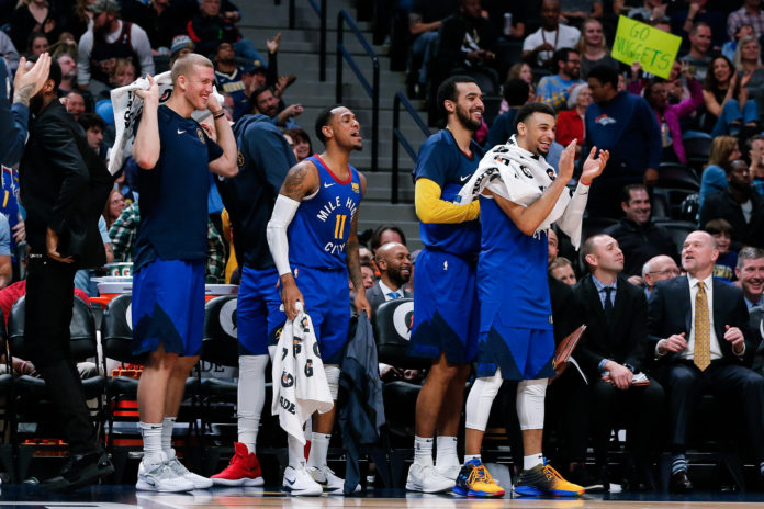 Denver Nuggets forward Mason Plumlee (24) and guard Monte Morris (11) and forward Trey Lyles (7) and guard Jamal Murray (27) react from the bench after a play in the fourth quarter against the Orlando Magic at the Pepsi Center.