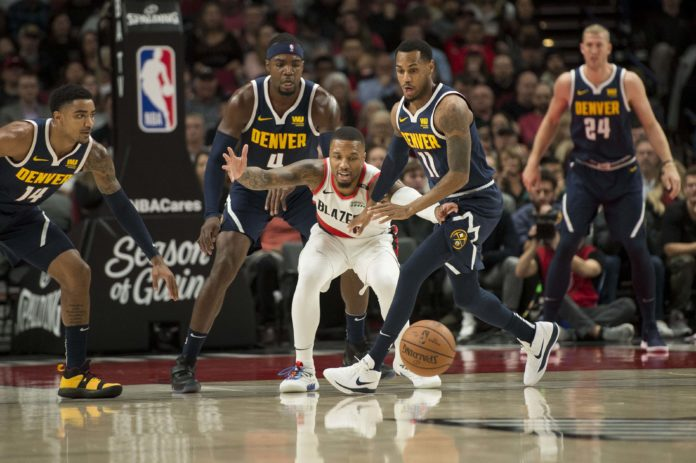 Portland Trail Blazers guard Damian Lillard (0) loses control of the basketball as he is guarded by Denver Nuggets guard Monte Morris (11) during the first half at Moda Center.