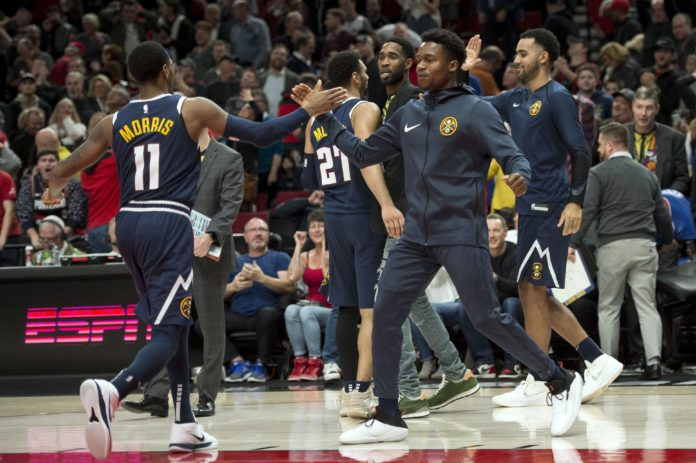 The Denver Nuggets bench congratulates teammates after a game against the Portland Trail Blazers at Moda Center.