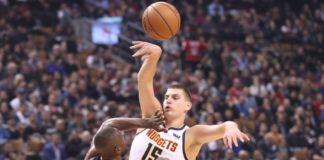 Denver Nuggets center Nikola Jokic (15) passes the ball under defensive coverage by Toronto Raptors forward Serge Ibaka (9) in the first quarter at Scotiabank Arena.