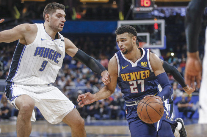 Denver Nuggets guard Jamal Murray (27) drives around Orlando Magic center Nikola Vucevic (9) during the first quarter at Amway Center.