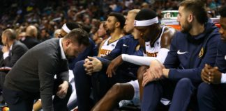 Denver Nuggets forward Paul Millsap (4) gets looked at by a trainer on the bench after being stepped on during the game against the Charlotte Hornets at Spectrum Center.