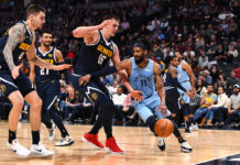 Memphis Grizzlies guard Mike Conley (11) drives at Denver Nuggets forward Juan Hernangomez (41) and center Nikola Jokic (15) in the second half at the Pepsi Center.