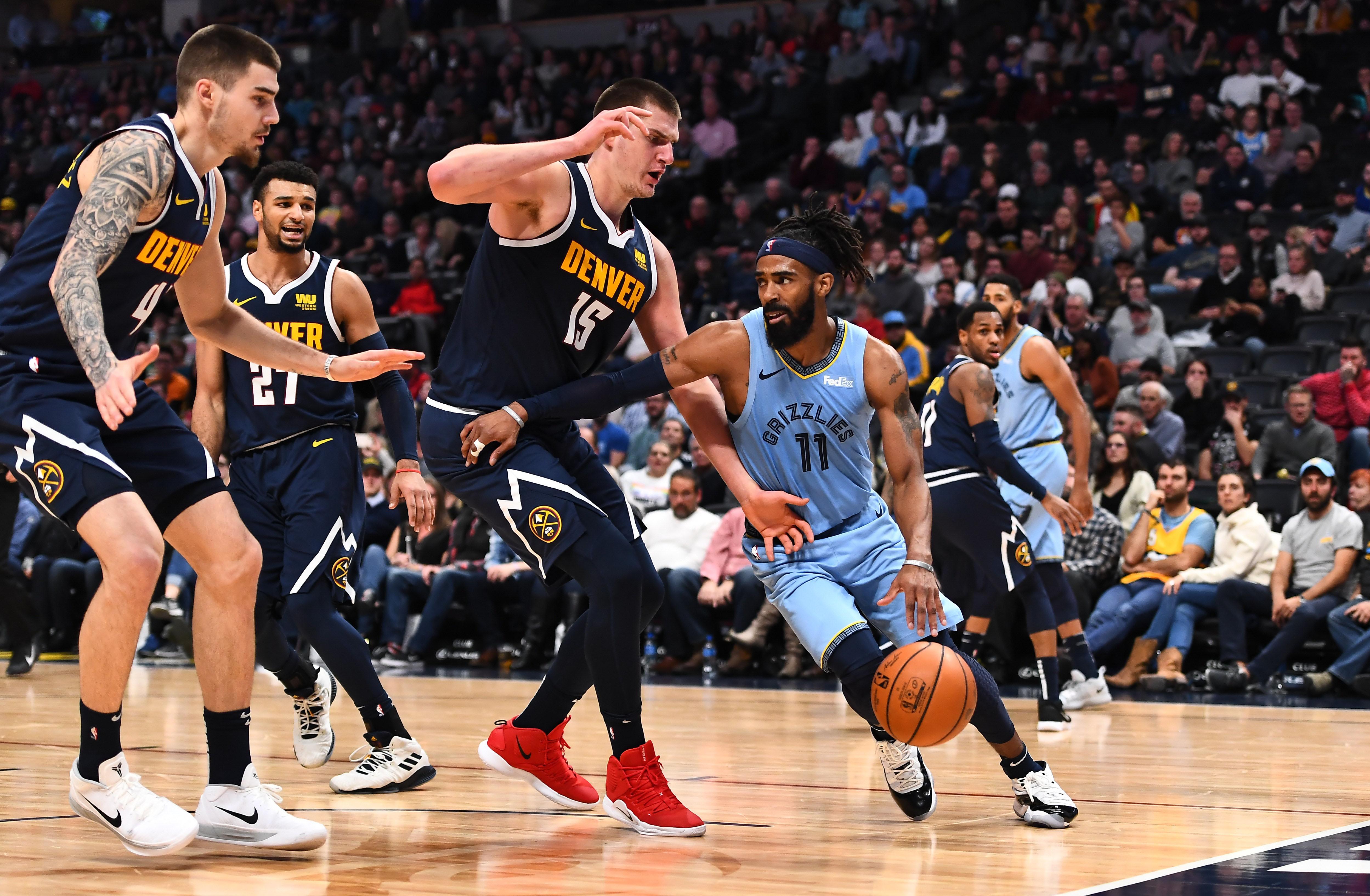 Memphis Grizzlies guard Mike Conley (11) drives at Denver Nuggets forward Juan Hernangomez (41) and center Nikola Jokic (15) in the second half at the Pepsi Center.