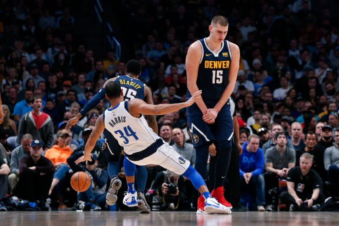 Dallas Mavericks guard Devin Harris (34) falls to the court as Denver Nuggets center Nikola Jokic (15) screens for guard Malik Beasley (25) in the fourth quarter at the Pepsi Center.