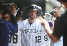 Colorado Rockies first baseman Mark Reynolds (12) celebrates with teammates in the dugout after hitting a two run home run during the sixth inning against the Pittsburgh Pirates at Coors Field.