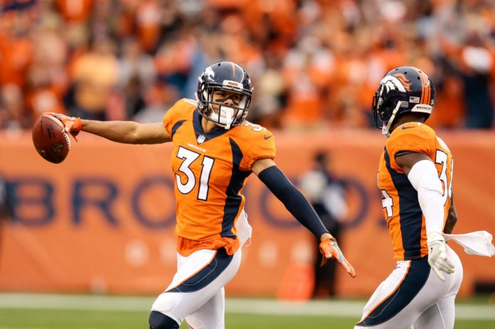Denver Broncos strong safety Justin Simmons (31) celebrates with safety Will Parks (34) after an interception in the fourth quarter against the Oakland Raiders at Sports Authority Field at Mile High.