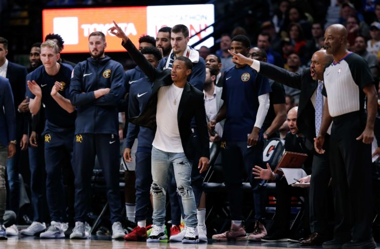 Denver Nuggets guard Isaiah Thomas (center) reacts from the bench with teammates in the fourth quarter against the Toronto Raptors at the Pepsi Center.