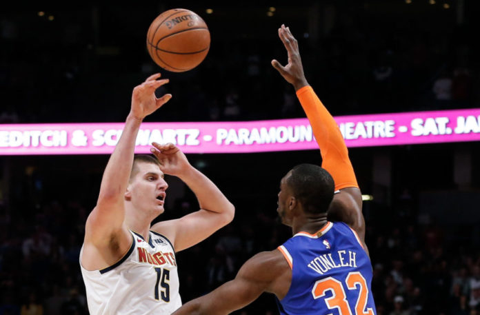 Denver Nuggets center Nikola Jokic (15) passes the ball over New York Knicks forward Noah Vonleh (32) in the first quarter at the Pepsi Center.