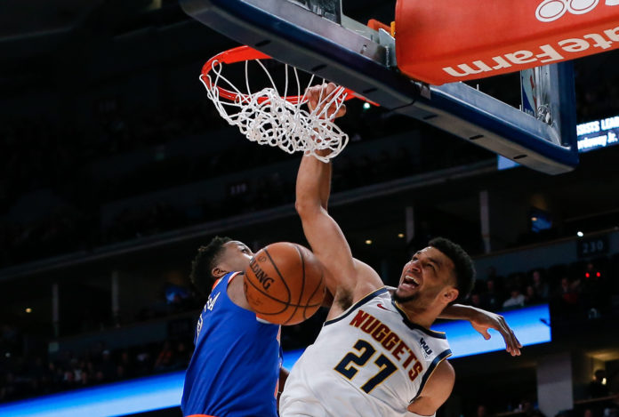Denver Nuggets guard Jamal Murray (27) dunks the ball against New York Knicks guard Frank Ntilikina (11) in the first quarter at the Pepsi Center.