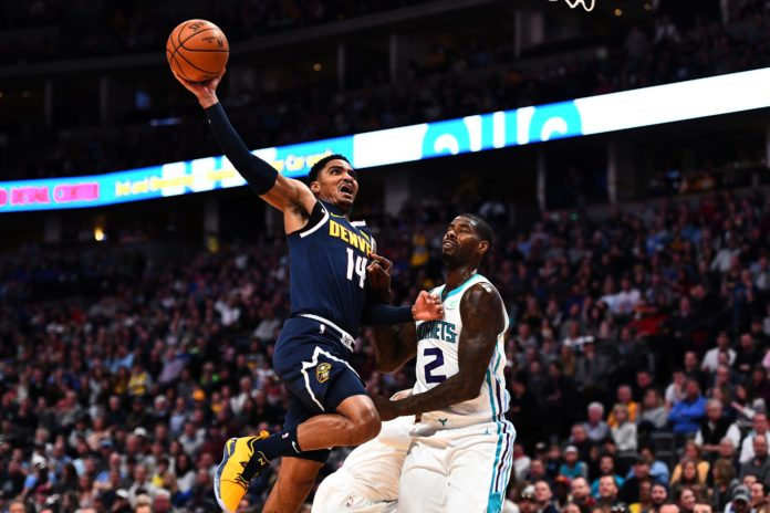 Denver Nuggets guard Gary Harris (14) attempts a shot over Charlotte Hornets forward Marvin Williams (2) in the second quarter at the Pepsi Center.