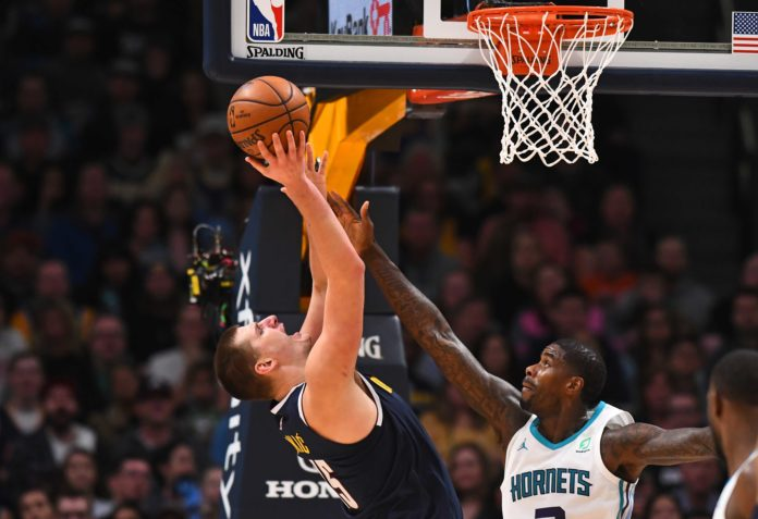 Charlotte Hornets forward Marvin Williams (2) reaches for the ball over Denver Nuggets center Nikola Jokic (15) in the second half at the Pepsi Center.