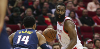 Houston Rockets guard James Harden (13) dribbles the ball against Denver Nuggets guard Gary Harris (14) during the first quarter at Toyota Center.