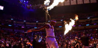Denver Nuggets forward Torrey Craig (3) stretches as flames are seen while members of the Miami Heat are introduced at American Airlines Arena.