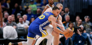 Golden State Warriors guard Stephen Curry (30) and Denver Nuggets forward Mason Plumlee (24) battle for the ball in the second quarter at the Pepsi Center.