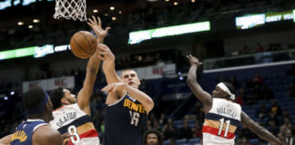 ; Denver Nuggets center Nikola Jokic (15) passes as he is defended by New Orleans Pelicans center Jahlil Okafor (8) and guard Jrue Holiday (11) during the second quarter at the Smoothie King Center.