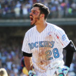 Colorado Rockies third baseman Nolan Arenado (28) celebrates after hitting a walk off three run home run to complete the cycle during the ninth inning against the San Francisco Giants at Coors Field.