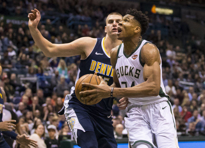 Milwaukee Bucks forward Giannis Antetokounmpo (34) drives for a shot around Denver Nuggets center Nikola Jokic (15) during the fourth quarter at BMO Harris Bradley Center.