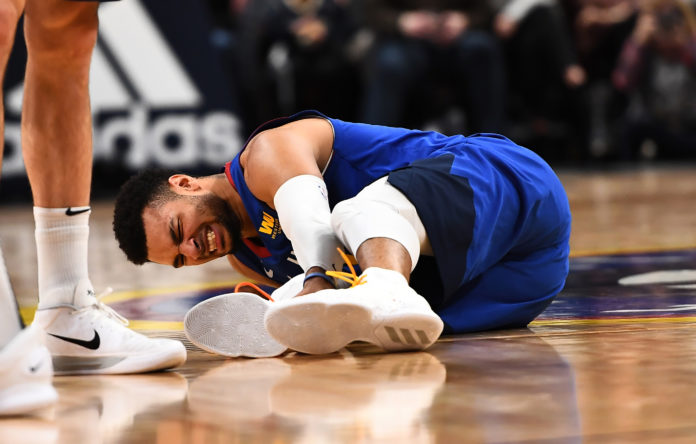 Denver Nuggets guard Jamal Murray (27) lays injured on the court in the fourth quarter against the San Antonio Spurs at the Pepsi Center.