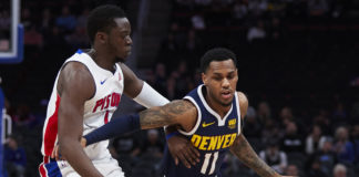 Denver Nuggets guard Monte Morris (11) dribbles the ball defended by Detroit Pistons guard Reggie Jackson (1) in the first half at Little Caesars Arena.