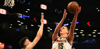 Denver Nuggets center Nikola Jokic (15) shoots against Brooklyn Nets forward Rodions Kurucs (00) during the first half at Barclays Center.