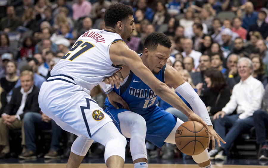 Denver Nuggets guard Jamal Murray (27) and Dallas Mavericks guard Jalen Brunson (13) fight for the loose ball during second quarter at the American Airlines Center.
