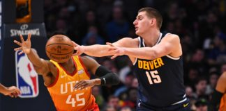 Denver Nuggets center Nikola Jokic (15) passes the ball past Utah Jazz guard Donovan Mitchell (45) in the second quarter at the Pepsi Center.