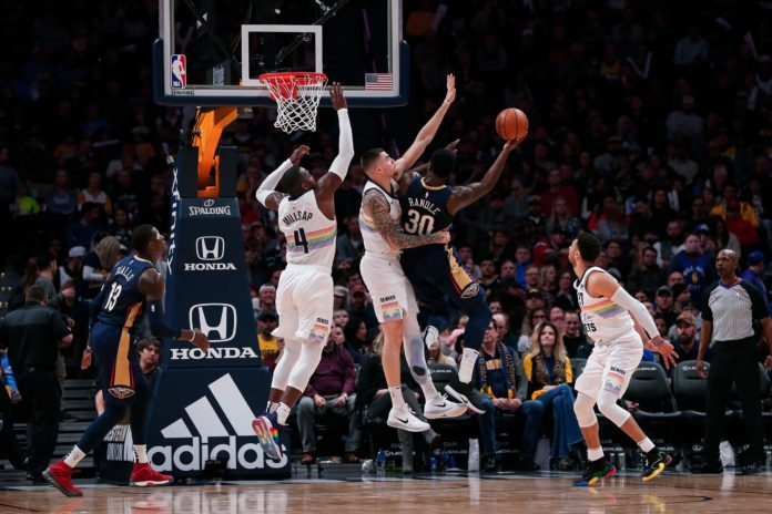 Denver Nuggets forward Juancho Hernangomez (41) and forward Paul Millsap (4) defend as New Orleans Pelicans center Julius Randle (30) drives to the net as guard Jamal Murray (27) looks on in the second quarter at the Pepsi Center.