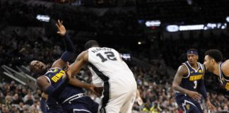 Denver Nuggets power forward Paul Millsap (left) draws a charge from San Antonio Spurs power forward LaMarcus Aldridge (12) during the first half at AT&T Center.