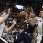 Denver Nuggets point guard Isaiah Thomas (0) drives to the basket as San Antonio Spurs point guard Derrick White (4) and Jakob Poeltl (left) defend during the first half at AT&T Center.